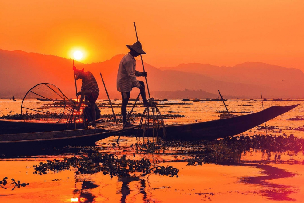 Fishermen maneuver their boats with only one leg in Inle Lake
